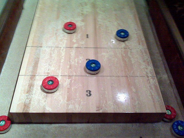 Shuffleboard table with pucks